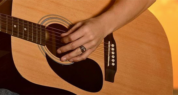 close up of woman playing guitar