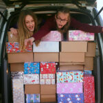van full of boxes with two volunteers
